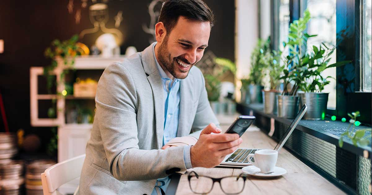 male remote working at coffee shop on phone