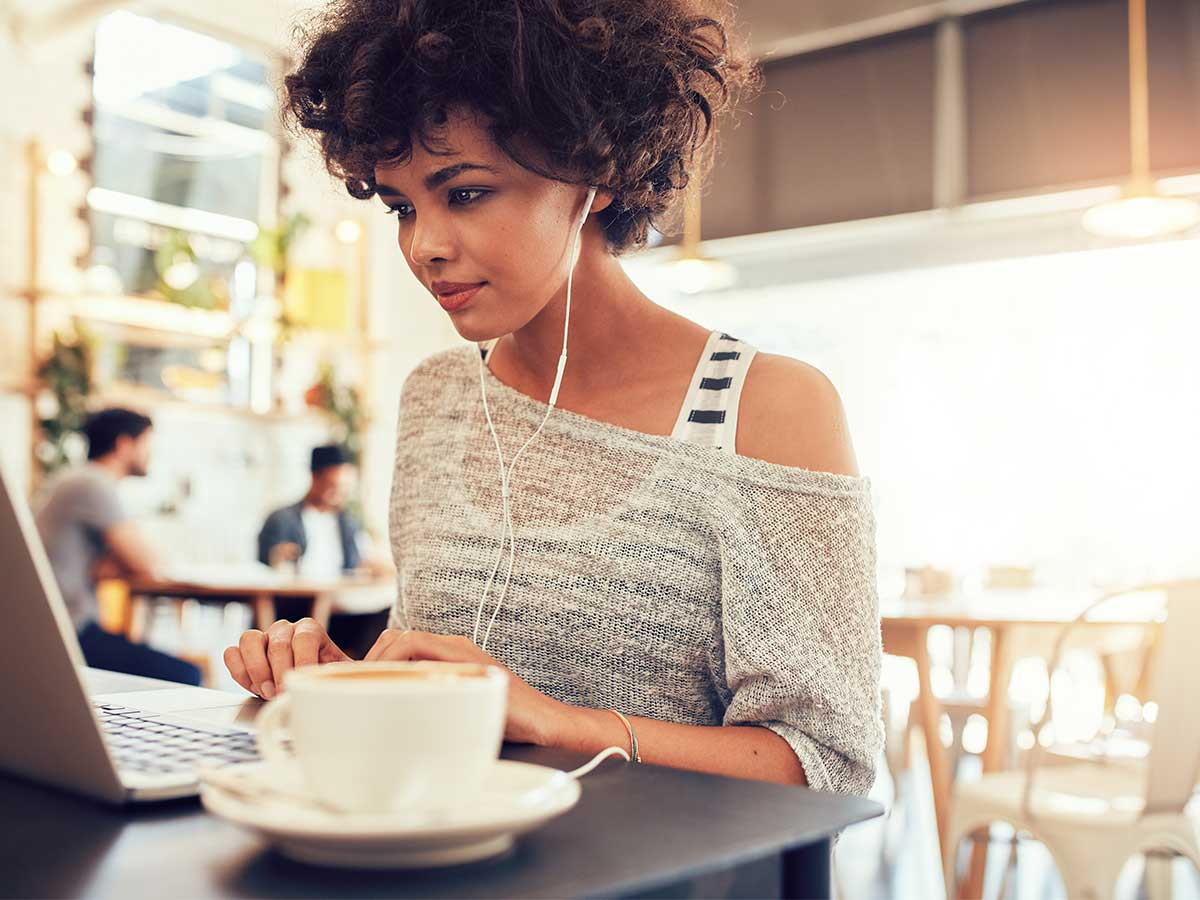 woman at coffee shop on a remote working schedule